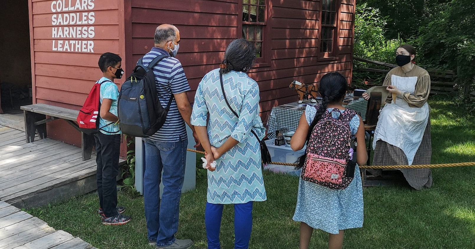a family enjoys a guided experience with a costumed educator at Black Creek Pioneer Village