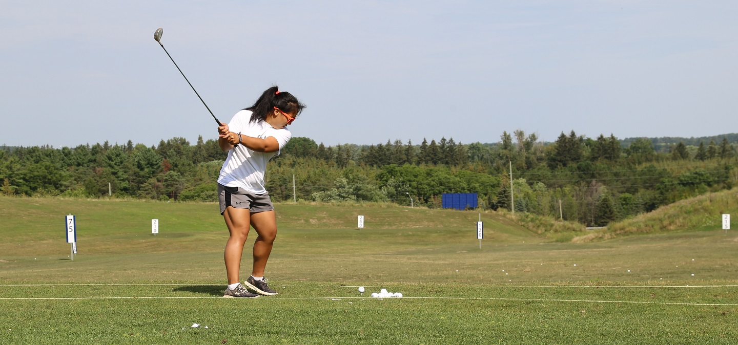 female golfer practices on driving range at bruce's mill conservation park