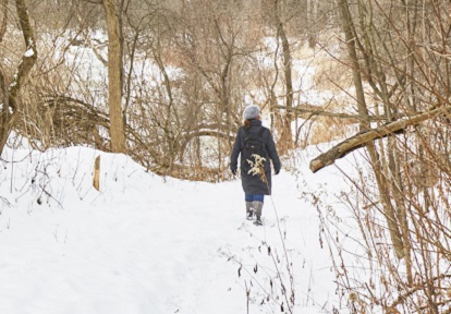 hiker explores snow covered trails at Kortright Centre for Conservation in winter