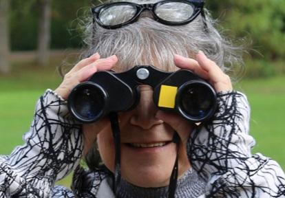 senior woman bird watching with binoculars