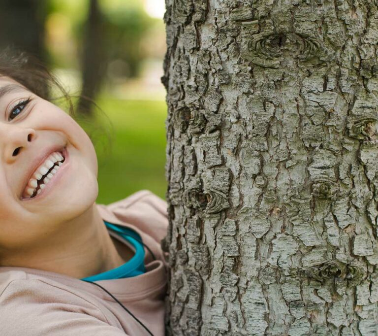 A little girl is smiling hugging a tree