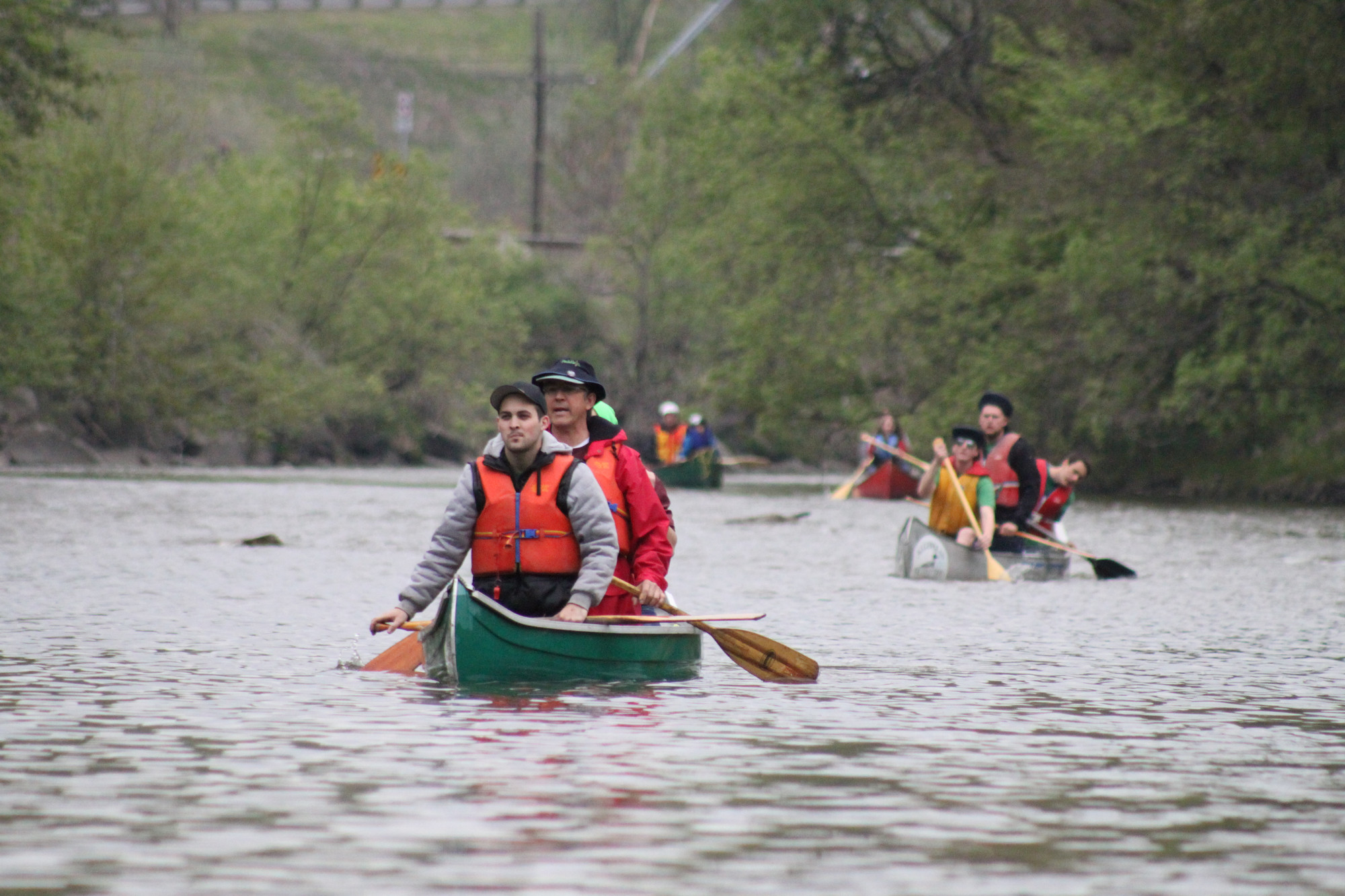 People in canoes paddling down a river