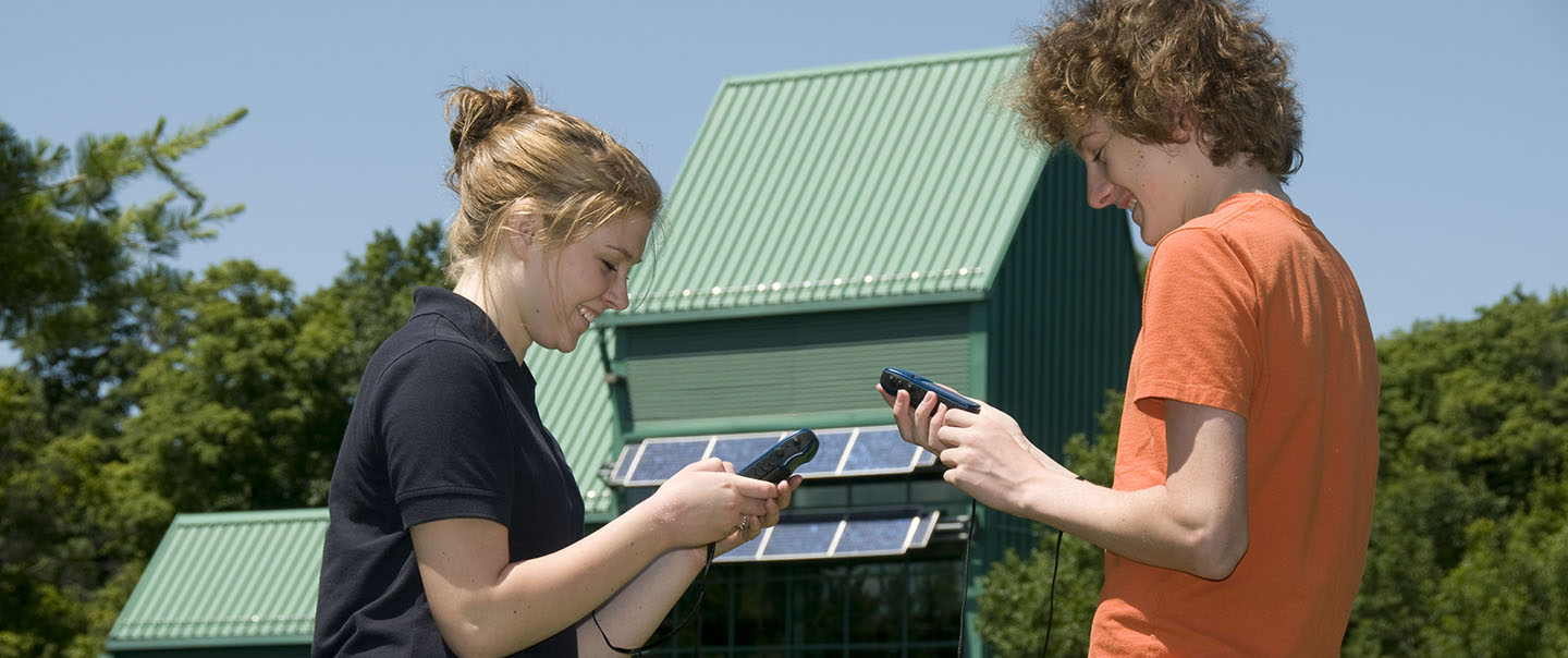 high school students use GPS unit to find geocache