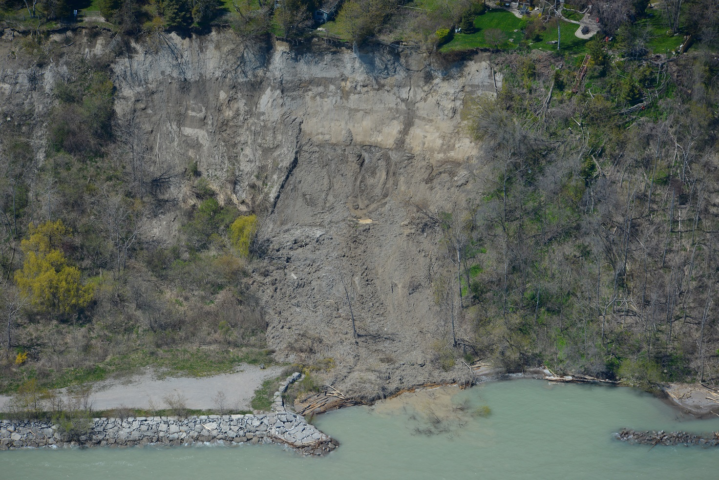 This image was taken from a helicopter and shows a landslide that has settled near the base of a very tall section of the Scarborough Bluffs. At the bottom of the photo, Lake Ontario is visibly turbid due to soil from the landslide being washed into the water. At the bottom left of the image is an dirt access road behind a shoreline revetment structure constructed of large 5 tonne armourstone blocks. The face of the bluff on either side of the slope failure is vegetated with shrubs and trees.