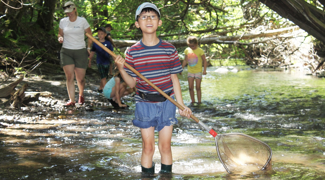 a young boy explores at stream at Claremont Field Centre nature day camps