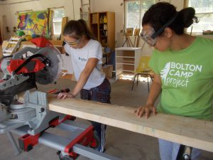 Two young women sawing plank of wood