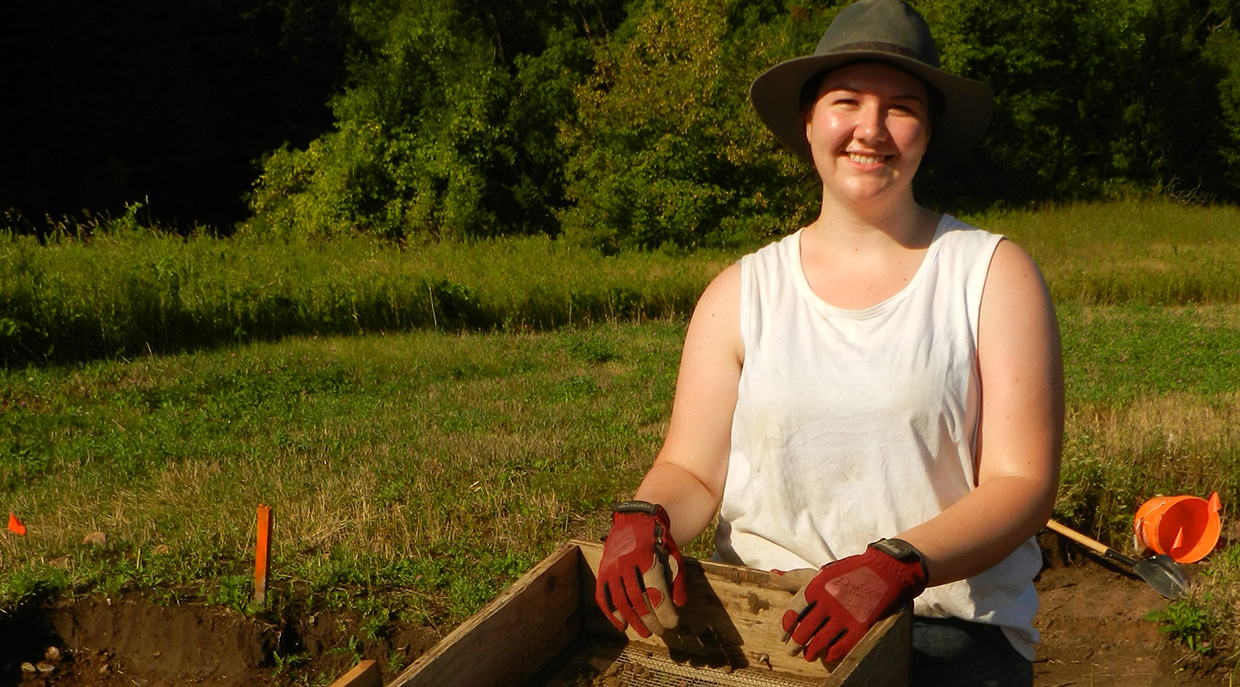 female Indigenous student works on a site excavation at the Boyd Archaeological Field School