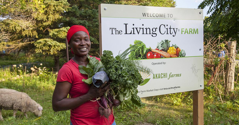 farmer displays produce at Living City Farm