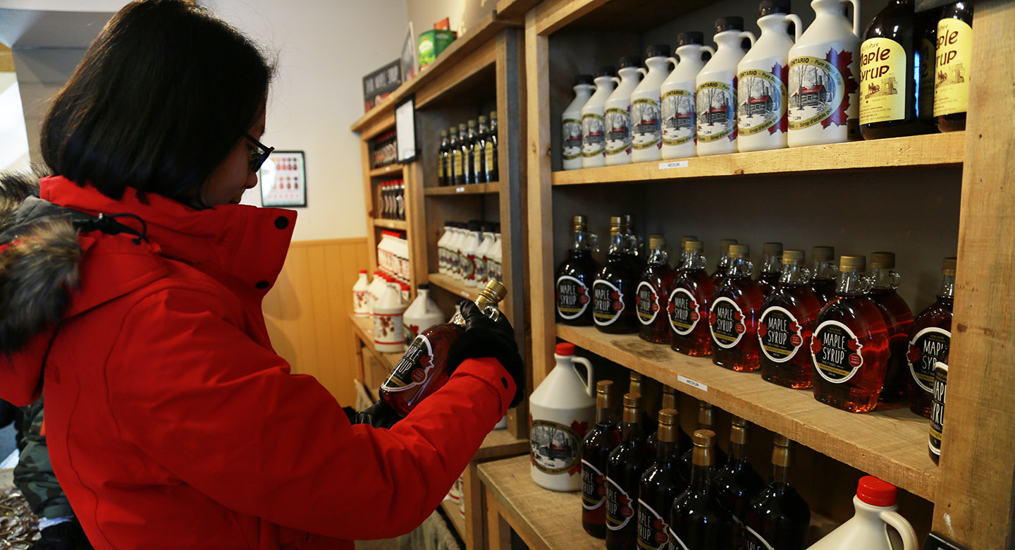 woman shopping for maple syrup at gift store