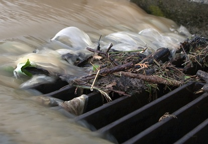 stormwater and debris rush into sewer grate