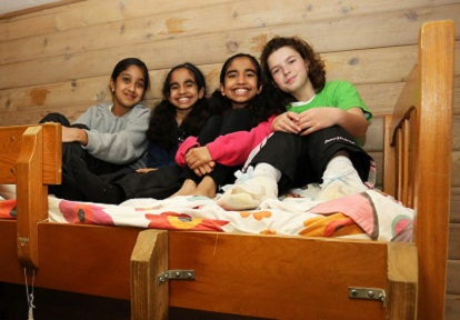 girls sit on bunk bed during overnight visit at Claremont Field Centre