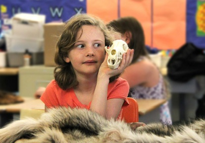 girl poses with small animal skull during Watershed on Wheels program