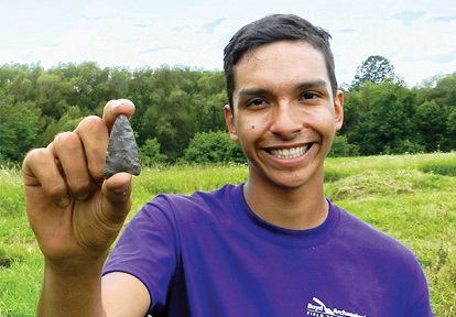 student at Boyd Archaeological Field School holds Indigenous artifact