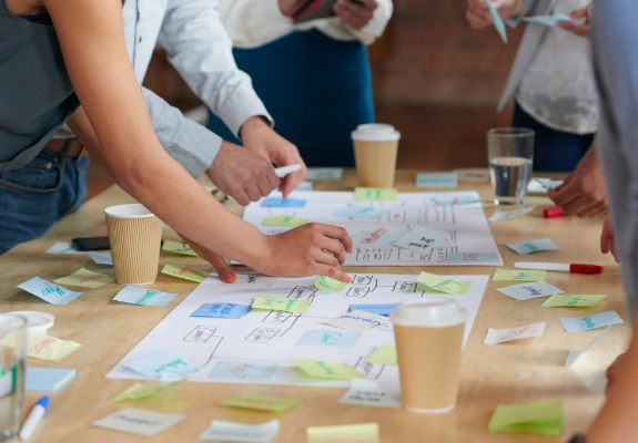 A group of people add sticky notes to two charts on a table