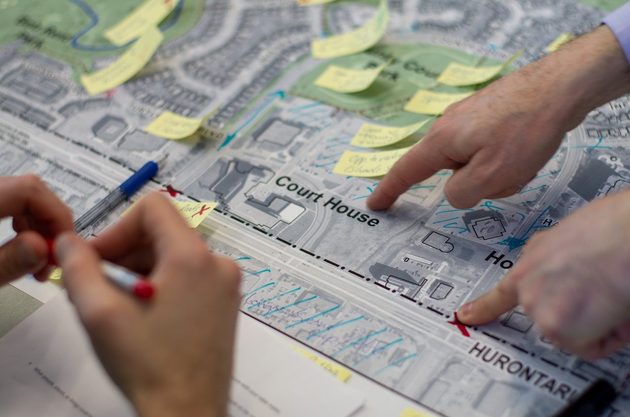 3 hands pointing and writing on a map of county court with sticky notes on it