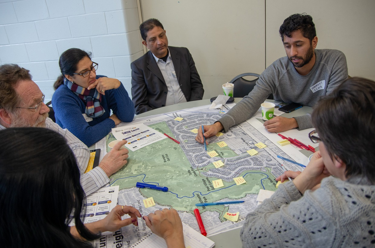 group of participants sitting around a large map of county court neighbourhood and making notes on the map