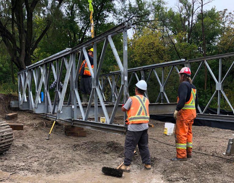 construction crew installs temporary bridge