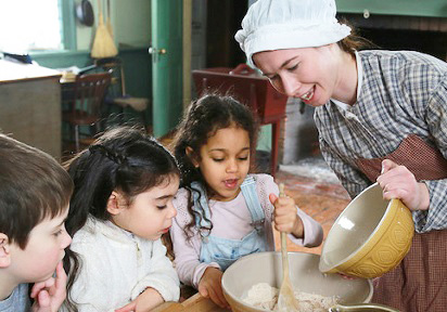 history actor in 19th century costume demonstrates Victorian baking for visitors at Black Creek Pioneer Village