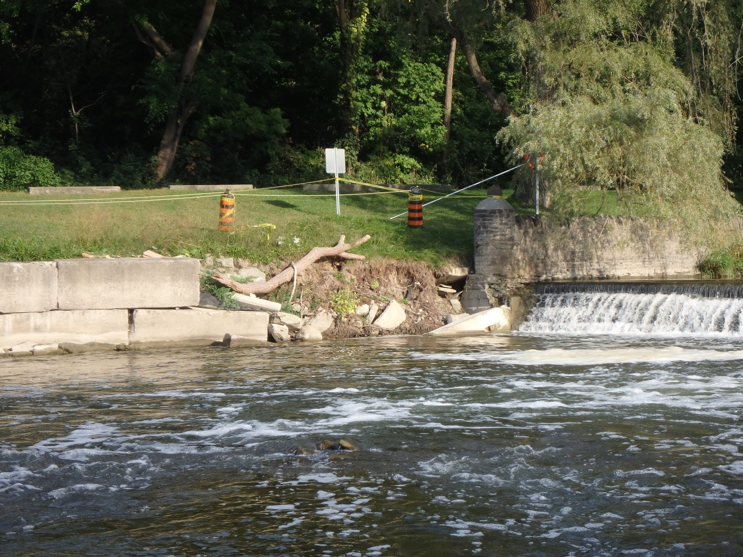 Photo showing river bank erosion along failing portion of retaining wall, adjacent to Home Smith Park weir