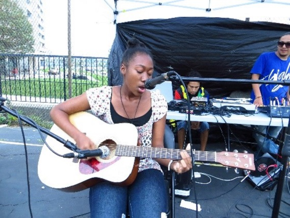 young musician performs at Black Creek SNAP pop-up park event for the San Romanoway Towers revival project in 2013