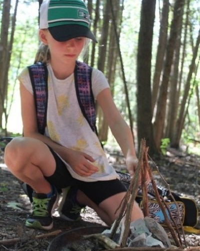 summer camper learns to build a campfire at Claremont Nature Centre