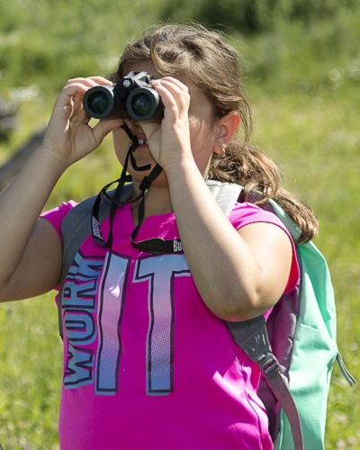 camper learns to use binoculars during outdoor summer nature camp at Claireville Conservation Area