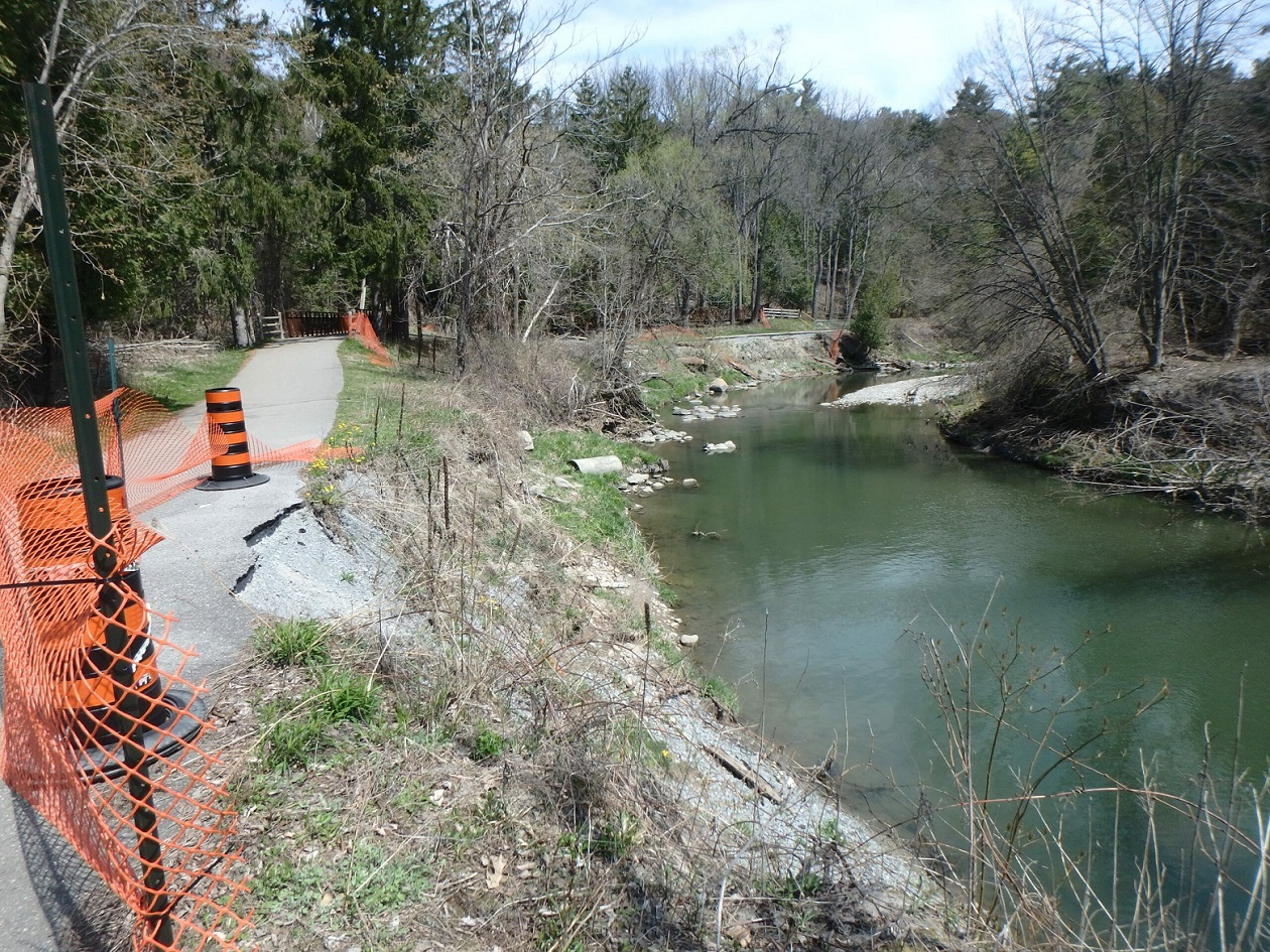 Crumbling asphalt trail within project area beside Highland Creek