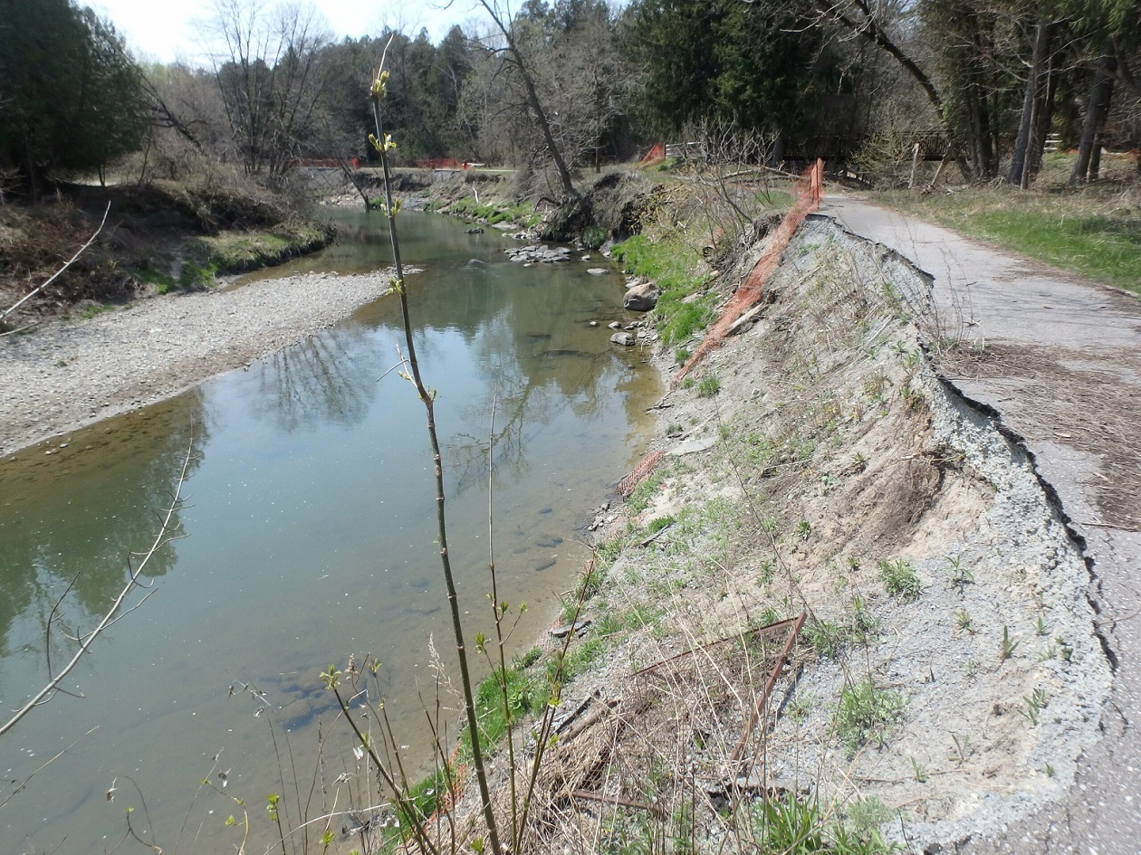 Crumbling asphalt trail facing upstream within work area