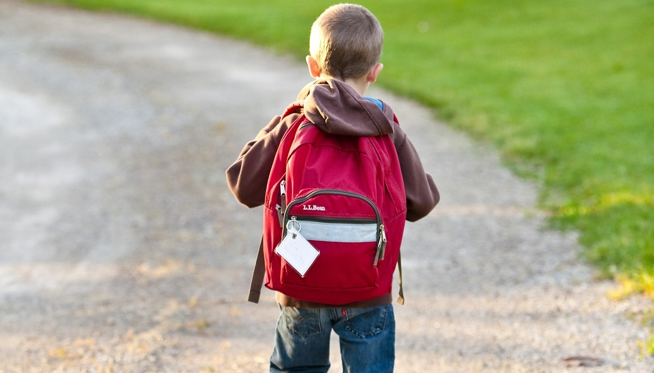 child with backpack walks to school