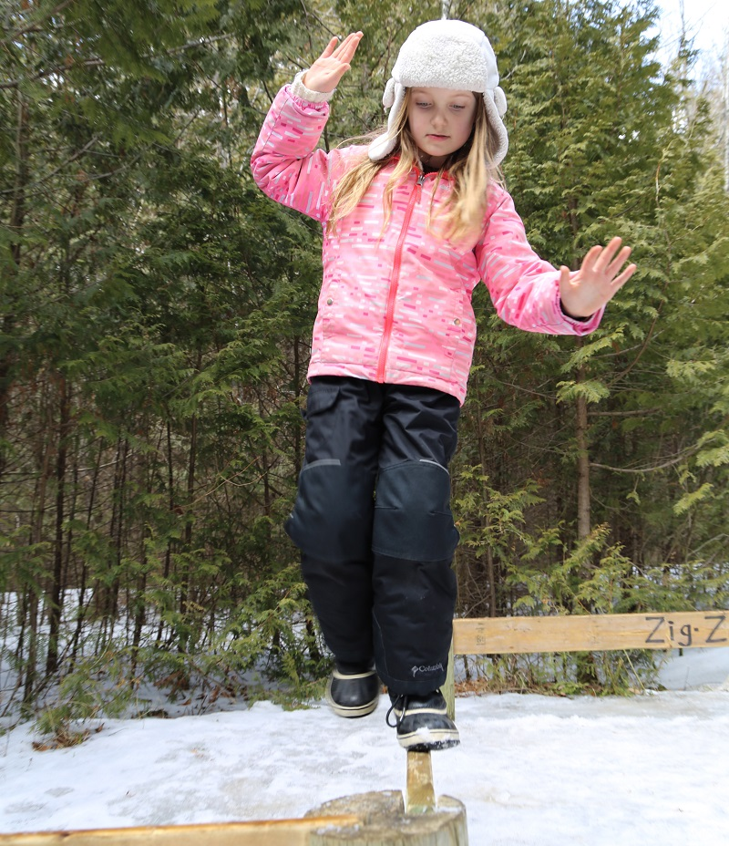 student walks on outdoor balance beam during winter mini camp at Claremont Nature Centre