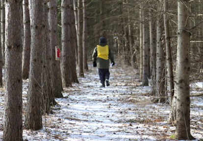 student explores forest trail during TRCA outdoor winter camp